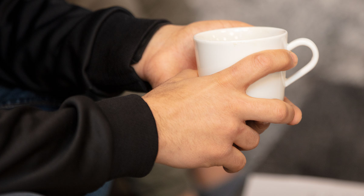 Närbild på händer som håller i en vit kaffekopp.