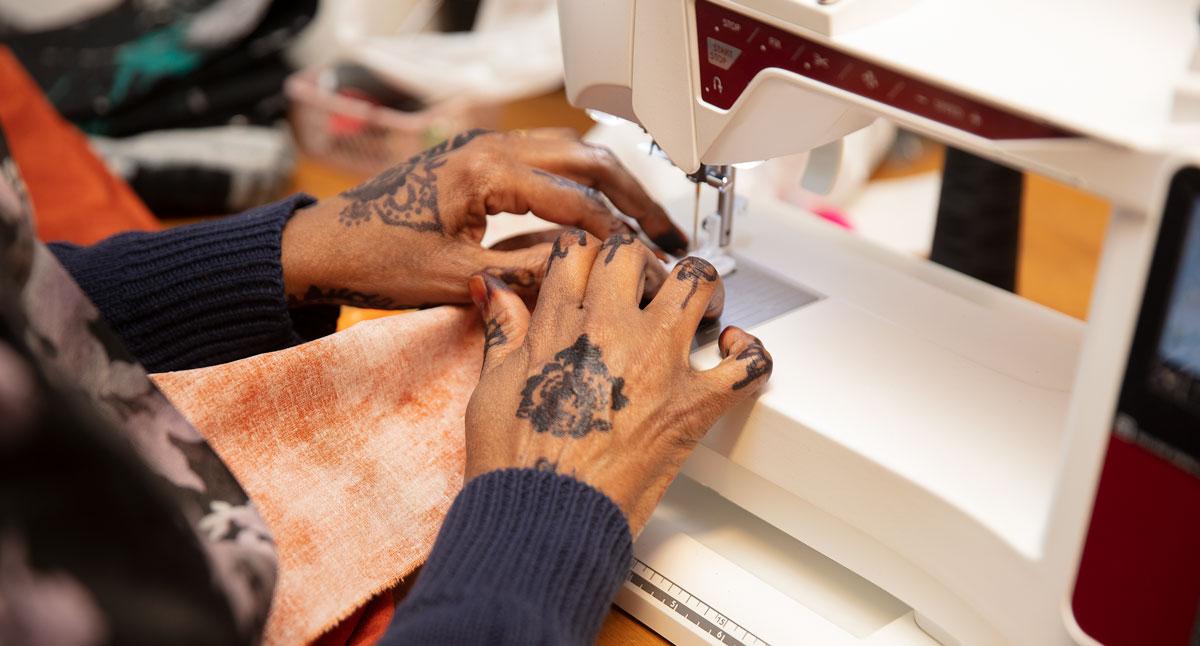 Närbild på händer som syr på symaskin.