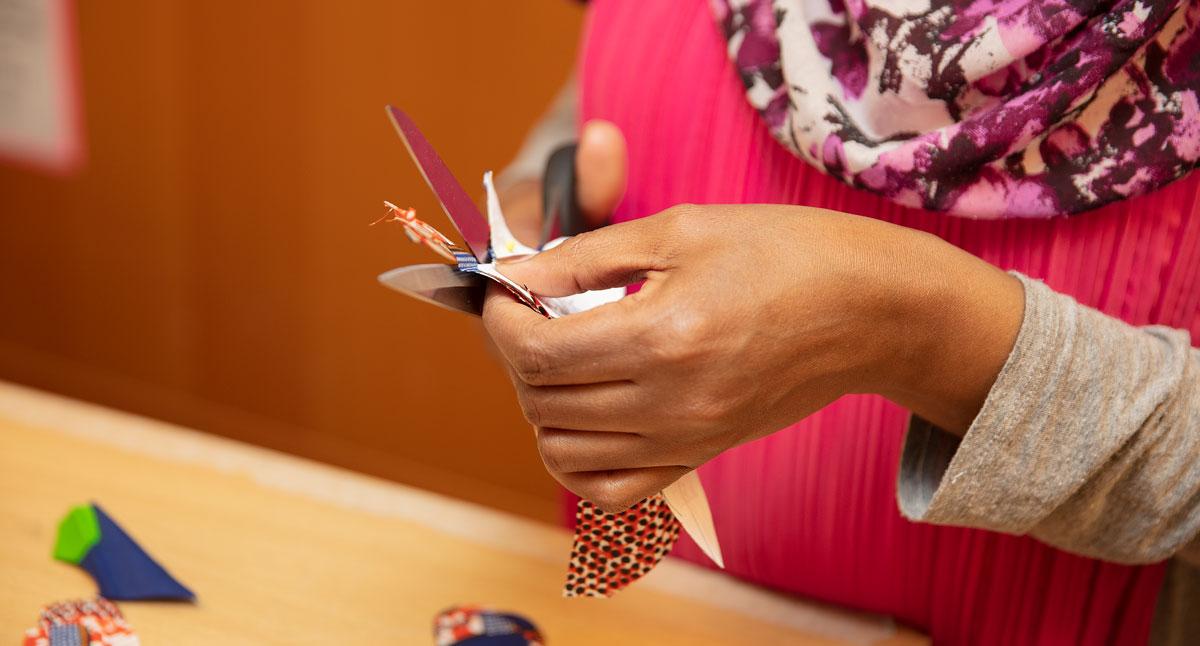 Närbild på händer som klipper med sax i tyg.
