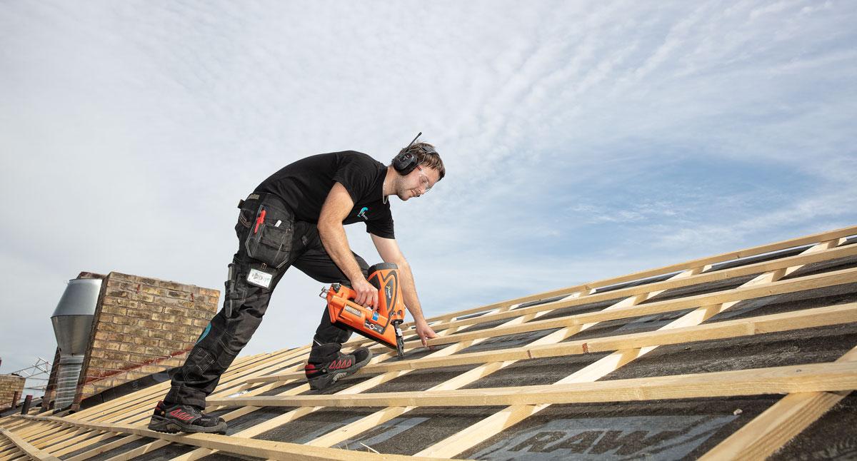 Byggarbetare jobbar med att lägga nytt tak på hus.