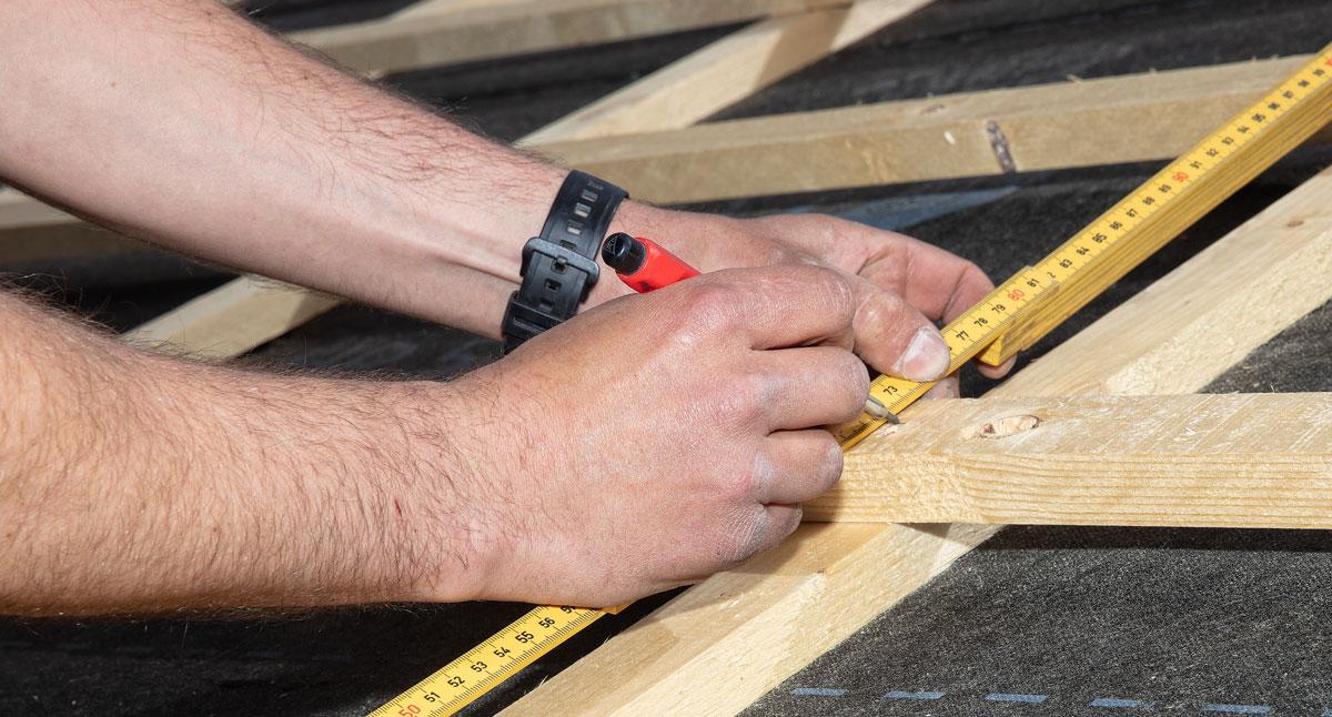 Närbild på händer som mäter med tumstock.
