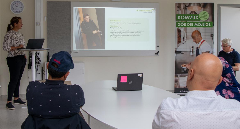 kvinna står vid ett ståbord med en dator på och visar en presentation.